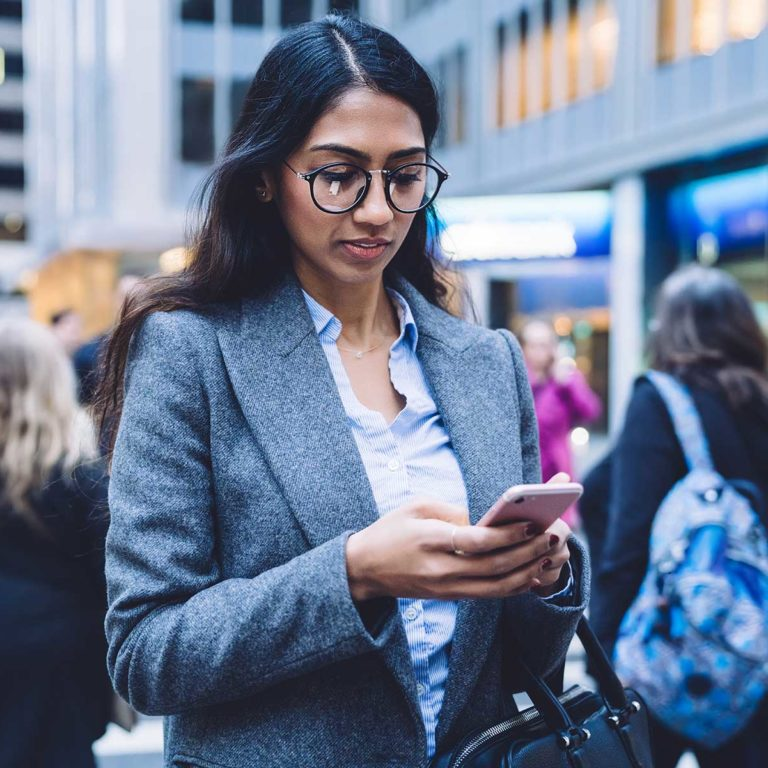 Woman texting in busy street Canadian Immigration Lawyers
