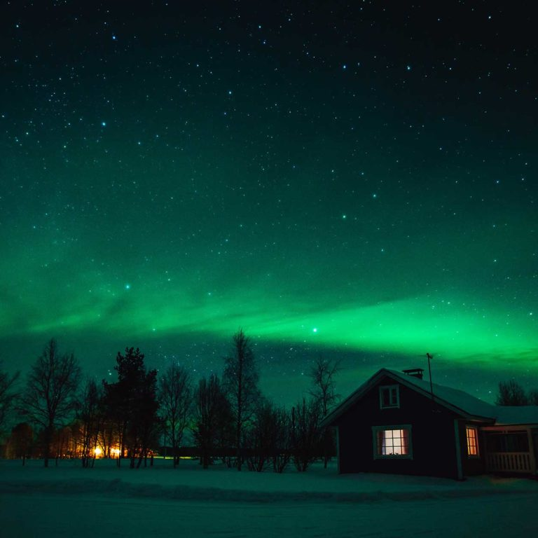 northern lights aurora borealis over cottage in la Borders Immigration Law Firm